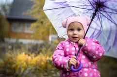 Ένα μικρό κορίτσι περπατά με μια ομπρέλα στη βροχή στη χώρα στοκ εικόνες