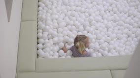 Ένα μικρό κορίτσι πηδά σε μια λίμνη με μια δέσμη των άσπρων σφαιρών απόθεμα βίντεο