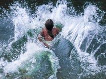 Ένα μικρό κορίτσι πηδά στο νερό στοκ φωτογραφίες