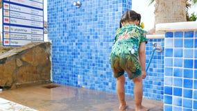 Ένα μικρό κορίτσι πλένει μακριά την άμμο κάτω από ένα ντους απόθεμα βίντεο