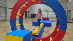 Ένα μικρό κορίτσι που ισορροπεί σε μια ακτίνα γυμναστικής στοκ εικόνα με δικαίωμα ελεύθερης χρήσης