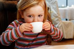 Ένα μικρό κορίτσι που πίνει από μια φλυτζάνα τσαγιού στοκ φωτογραφία