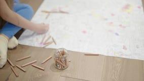 Ένα μικρό κορίτσι που χρωματίζει μια μεγάλη εικόνα στο πάτωμα απόθεμα βίντεο