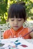 Ένα μικρό κορίτσι που χρωματίζει στο σπίτι τον κήπο Στοκ εικόνες με δικαίωμα ελεύθερης χρήσης