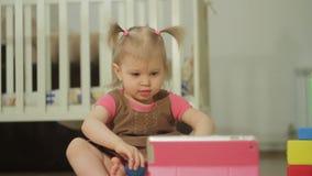 Ένα μικρό κορίτσι προσέχει τα κινούμενα σχέδια σε μια ηλεκτρονική ταμπλέτα απόθεμα βίντεο