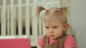 Ένα μικρό κορίτσι προσέχει τα κινούμενα σχέδια σε μια ηλεκτρονική ταμπλέτα φιλμ μικρού μήκους