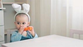 Ένα μικρό κορίτσι σε ένα άσπρο κοστούμι λαγουδάκι κάθεται στον πίνακα και ένα καρότο απόθεμα βίντεο