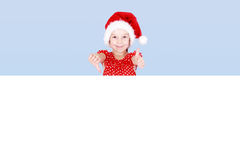 Ένα μικρό κορίτσι σε ένα κόκκινα φόρεμα και ένα καπέλο Άγιου Βασίλη παρουσιάζει δάχτυλό του στο διάστημα αγγελιών Στοκ Εικόνες