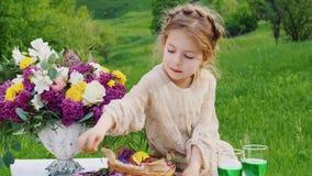 Ένα μικρό κορίτσι σε ένα έξυπνο φόρεμα κάθεται σε έναν πίνακα που διακοσμείται με τα λουλούδια και τρώει μια σοκολάτα finge Ημέρα φιλμ μικρού μήκους