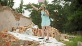 Ένα μικρό κορίτσι σε μια μάσκα αερίου στις καταστροφές ενός κτηρίου και μιας εκμετάλλευσης προς μια κούκλα και τα μπαλόνια απόθεμα βίντεο
