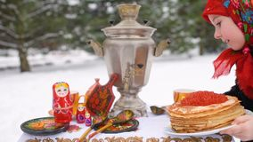 Ένα μικρό κορίτσι σε ένα παλτό γουνών και σε ένα μαντίλι στο ρωσικό ύφος βάζει σε έναν εορταστικό πίνακα ένα πιάτο με τις τηγανίτ απόθεμα βίντεο