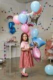 Ένα μικρό κορίτσι σε ένα ρόδινο σακάκι και μια φούστα σκονών κρατά ένα β Στοκ Εικόνες