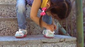 Ένα μικρό κορίτσι σκουπίζει τα σανδάλια της απόθεμα βίντεο