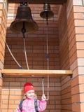 Ένα μικρό κορίτσι στα παλαιά χτυπώντας κουδούνια χαλκού Στοκ Φωτογραφία