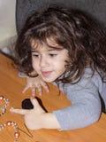 Ένα μικρό κορίτσι συμμετέχει στη ραπτική στον πίνακα πορτρέτο κινηματογραφήσεων σε πρώτο πλάνο ενός 3χρονου κοριτσιού στοκ εικόνα με δικαίωμα ελεύθερης χρήσης