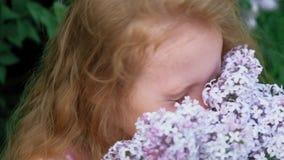 Ένα μικρό κορίτσι υπαίθρια σε ένα πάρκο ή έναν κήπο κρατά τα ιώδη λουλούδια Ιώδεις θάμνοι στο υπόβαθρο Καλοκαίρι, πάρκο απόθεμα βίντεο