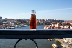 Ένα μικρό μπουκάλι του κρασιού του Πόρτο, στο υπόβαθρο του πανοράματος του Πόρτο, Πορτογαλία Εκλεκτική εστίαση, θολωμένο υπόβαθρο στοκ εικόνες