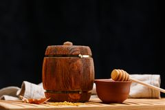 Ένα μικρό ξύλινο βυτίο με το μέλι μέσα και ένα κουτάλι σε έναν ξύλινο πίνακα σε ένα σκοτεινό υπόβαθρο barracking ζωή αγροτική ακό στοκ φωτογραφίες