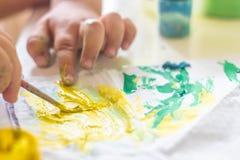 Ένα μικρό παιδί επισύρει την προσοχή τα χρώματα σε έναν πίνακα Στοκ φωτογραφία με δικαίωμα ελεύθερης χρήσης