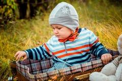 Ένα μικρό παιδί κάθεται σε μια βαλίτσα στοκ εικόνα με δικαίωμα ελεύθερης χρήσης