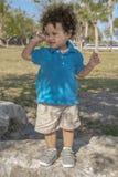 Ένα μικρό παιδί πάνω από έναν μεγάλο βράχο στο πάρκο κοιτάζει στο δικαίωμά του στοκ εικόνα με δικαίωμα ελεύθερης χρήσης