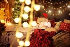 Ένα μικρό παιδί παιδιών διαβάζει ένα βιβλίο στο δωμάτιο Χριστουγέννων Στοκ εικόνα με δικαίωμα ελεύθερης χρήσης