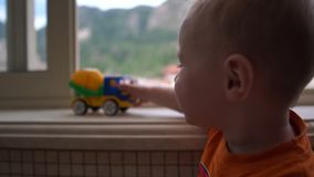 Ένα μικρό παιδί που στέκεται κοντά στο παράθυρο και που παίζει με το φορτηγό σε σε αργή κίνηση απόθεμα βίντεο