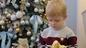 Ένα μικρό παιδί που τρώει μια μπανάνα κοντά στο χριστουγεννιάτικο δέντρο απόθεμα βίντεο