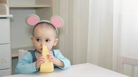 Ένα μικρό παιδί σε ένα γκρίζο κοστούμι ποντικιών μασά το κίτρινο τυρί με τις τρύπες στο βρεφικό σταθμό φιλμ μικρού μήκους