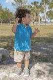 Ένα μικρό παιδί στέκεται επάνω σε έναν μεγάλο βράχο στο πάρκο, κοιτάζει στο αριστερό του στοκ φωτογραφία