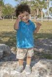 Ένα μικρό παιδί στέκεται επάνω σε έναν μεγάλο λίθο στο τοπικό πάρκο στοκ εικόνες