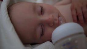 Ένα μικρό παιδί ύπνου βρίσκεται σε ένα κρεβάτι με τη μέτρηση του μπουκαλιού είναι στο στόμα του απόθεμα βίντεο