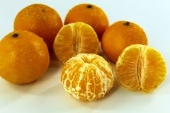 Ένα μικρό ποσό ξεφλούδισε και μη επεξεργασμένα tangerines σε ένα άσπρο υπόβαθρο στοκ εικόνες