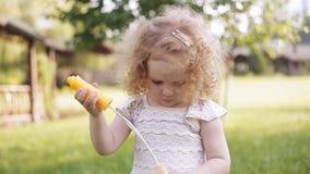 Ένα μικρό φυσώντας σαπούνι κοριτσιών βράζει, όμορφο σγουρό μωρό πορτρέτου κινηματογραφήσεων σε πρώτο πλάνο φιλμ μικρού μήκους