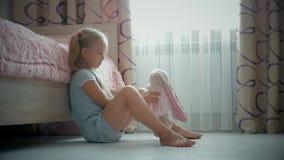 Ένα μικρό όμορφο κορίτσι και ένα κουνέλι παιχνιδιών στο φόρεμα στο σπίτι Οικογενειακές σχέσεις Το παιδί που αγκαλιάζει το καλό πα φιλμ μικρού μήκους