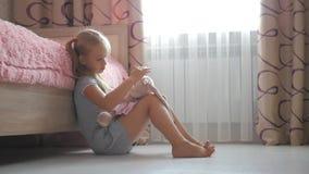 Ένα μικρό όμορφο κορίτσι και ένα κουνέλι παιχνιδιών στο φόρεμα στο σπίτι Οικογενειακές σχέσεις Το παιδί που αγκαλιάζει το καλό πα απόθεμα βίντεο