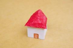 Ένα μικρό όμορφο σπίτι φιαγμένο από έγγραφο με μια κόκκινη στέγη, ακίνητη περιουσία σε μια πρότυπη έννοια Στοκ Εικόνες
