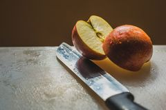 Ένα μισό έκοψε την κόκκινη Apple σε έναν πίνακα Chooping Στοκ Εικόνα