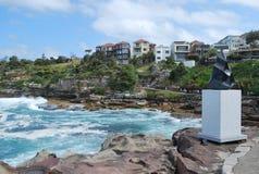 Ένα μνημείο και σπίτια στην ωκεάνια ακτή κοντά στη διάσημη παραλία Σίδνεϊ Bondi στοκ εικόνες