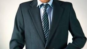 Ένα μοντέρνο άτομο ντύνει ένα κοστούμι, ισιώνει έναν δεσμό και ένα σακάκι φαίνεται κομψός απόθεμα βίντεο