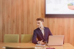 Ένα μοντέρνο άτομο σε ένα σακάκι και ένα πουκάμισο κάθεται στο γραφείο με τους συναδέλφους του και εργάζεται με τα έγγραφα στο γρ στοκ εικόνες με δικαίωμα ελεύθερης χρήσης