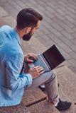 Ένα μοντέρνο αρσενικό freelancer με μια πλήρη γενειάδα και ένα κούρεμα, που φορά τα περιστασιακά ενδύματα, που λειτουργούν σε ένα Στοκ Φωτογραφία