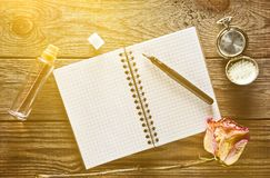Ένα μπουκάλι γυαλιού με το άρωμα, το σημειωματάριο και μια μάνδρα, ξηρά αυξήθηκε Στοκ Φωτογραφίες
