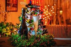 Ένα μπουκάλι και ένα ποτήρι της σαμπάνιας στο υπόβαθρο του χριστουγεννιάτικου δέντρου και των γιρλαντών Νέο ντεκόρ έτους ` s στοκ φωτογραφία με δικαίωμα ελεύθερης χρήσης