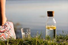 Ένα μπουκάλι νερό με το λεμόνι και ένα γυαλί Ένα πόσιμο νερό γυναικών Στοκ Εικόνες