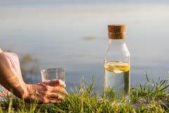 Ένα μπουκάλι νερό με το λεμόνι και ένα γυαλί Ένα πόσιμο νερό γυναικών Στοκ φωτογραφία με δικαίωμα ελεύθερης χρήσης