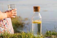 Ένα μπουκάλι νερό με το λεμόνι και ένα γυαλί Ένα πόσιμο νερό γυναικών Στοκ φωτογραφίες με δικαίωμα ελεύθερης χρήσης