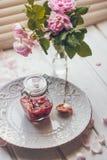 Ένα μπουκάλι της ροδαλής μαρμελάδας στο πιάτο με μια ανθοδέσμη κουταλιών και λουλουδιών στο ελαφρύ υπόβαθρο στοκ φωτογραφία