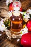 Ένα μπουκάλι του μηλίτη ξιδιού μηλίτη μήλων, των φρέσκων μήλων και του Apple-δέντρου ανθίζει σε ένα ξύλινο υπόβαθρο Ύφος χώρας Στοκ Φωτογραφία