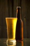 Ένα μπουκάλι της κρύας μπύρας σχεδίων με ένα γυαλί Στοκ Φωτογραφίες